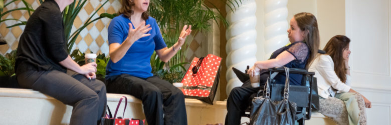 Image shows 2 women sitting next to each other, One is speaking with her hands. The other is listening. Across from them is a woman who is in a wheel chair who is also listening and holding a coffee cup. On the floor is a golden Labrador retriever service dog laying down relaxing.
