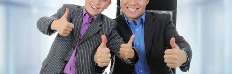 businessman with son at take your child to work date giving thumbs up to photograpgher