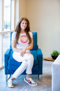 Mona Lisa Faris, publisher of DiversityComm, wearing white pants and a white Wonder Woman shirt while sitting in a blue chair.