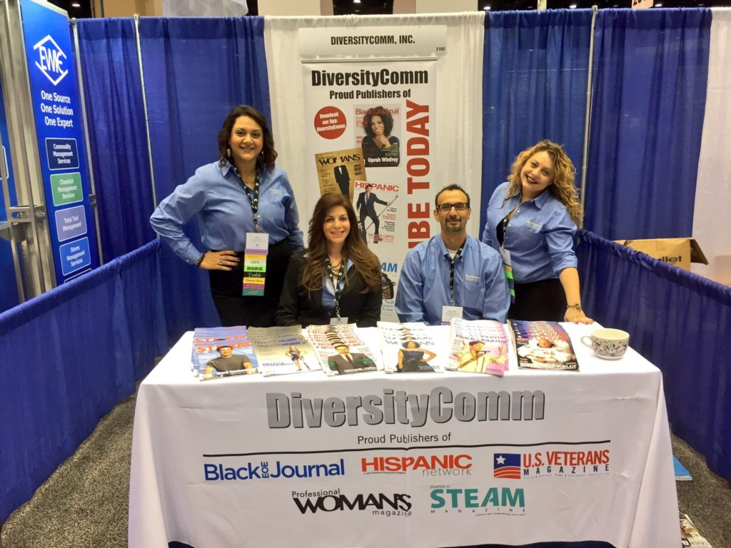 Mona Lisa Faris and her team members manning a DiversityComm information booth at a conference expo.